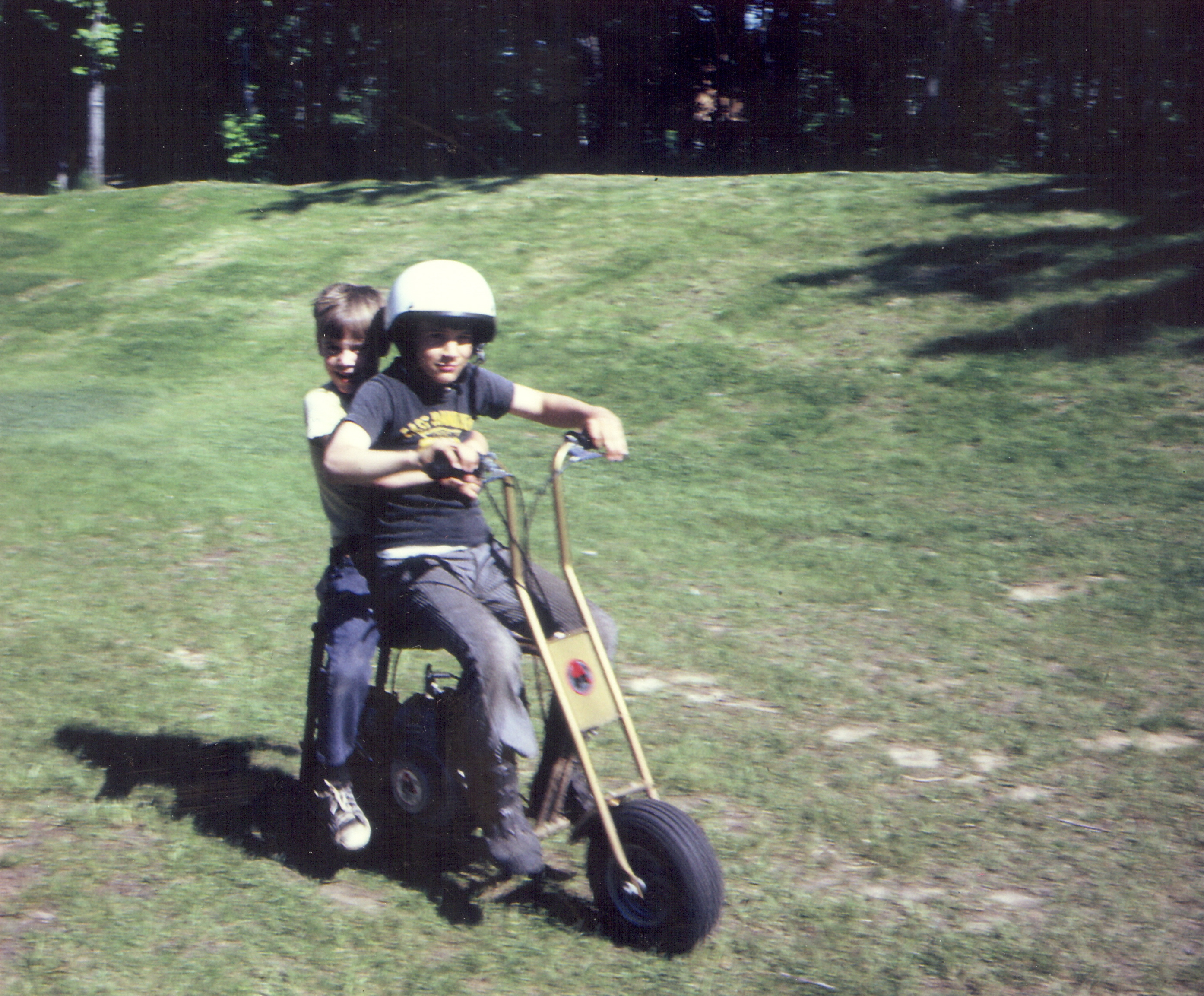 My brother John giving me my first ride on a minibike.